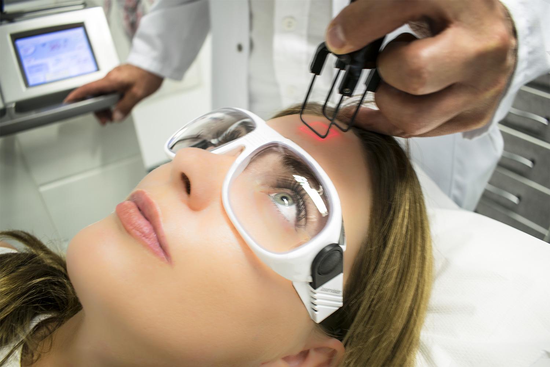 Dr. Michael Siegmund, Hautarzt in Salzburg, führt eine Laserbehandlung an einer Patientin durch.